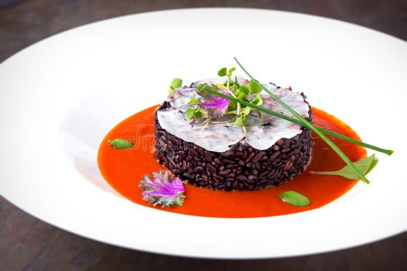 Risotto vom schwarzen Reis mit Fischen in der Tomatensauce Italienische Gaststätte menü stockfotografie