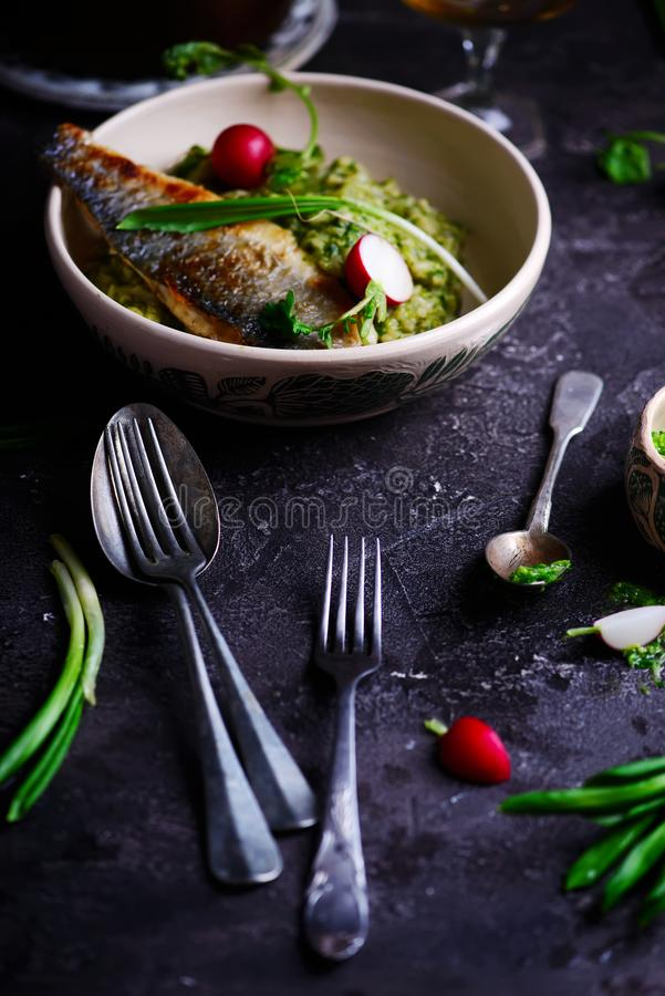 Risotto with wild garlic and sea bass.style rustic royalty free stock photos