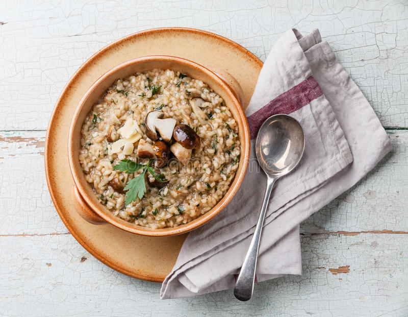 Risotto with wild mushrooms. With parsley and parmesan on blue background royalty free stock photos