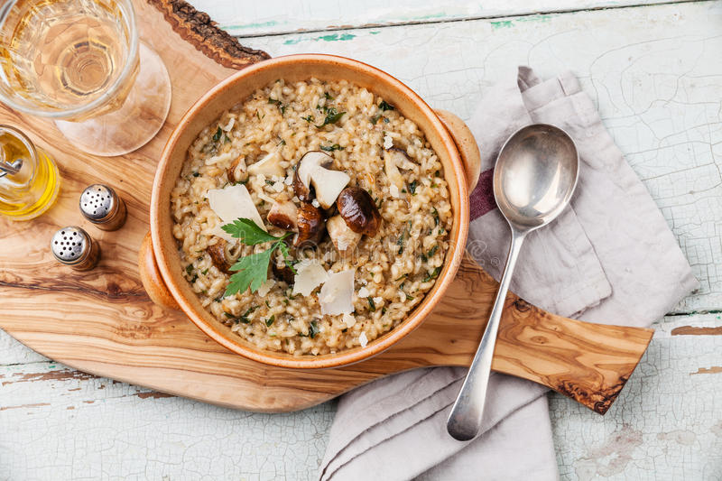 Risotto with wild mushrooms. With parsley and parmesan on olive wood board stock image