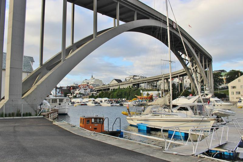 Risoy Bridge in Haugesund, Norway, Europe. HAUGESUND, NORWAY - AUGUST 7, 2015. The Risoy Bridge spanning over the Smedasundet. Some motorboats on the canal royalty free stock images