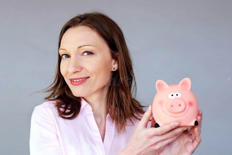 Risparmio dei soldi nessun porcellino salvadanaio di salvadanaio della tenuta della donna di sforzo immagine stock
