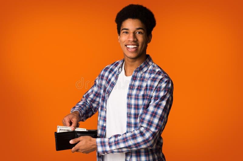 risparmio dei soldi Tipo afroamericano che mette le banconote nel portafoglio fotografia stock libera da diritti