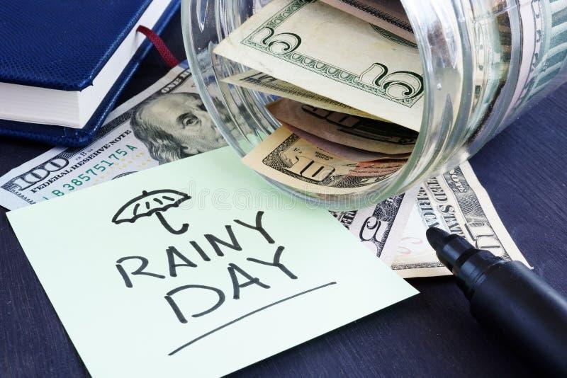 Risparmio del fondo di giorno piovoso Vaso con le fatture del dollaro immagine stock