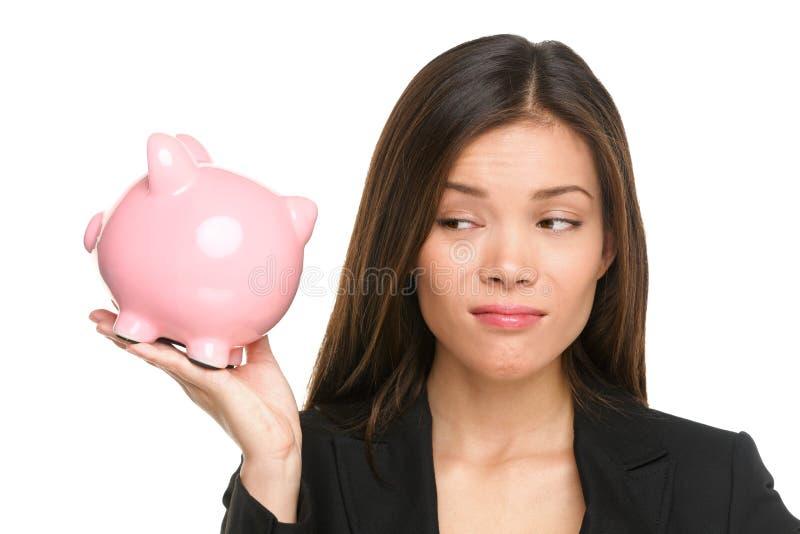 Risparmio del porcellino salvadanaio con la donna divertente infelice immagine stock