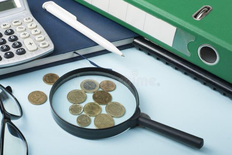 Risparmio domestico, concetto del bilancio Blocco note, lente d'ingrandimento, calcolatore e monete sulla tavola di legno della s immagine stock libera da diritti
