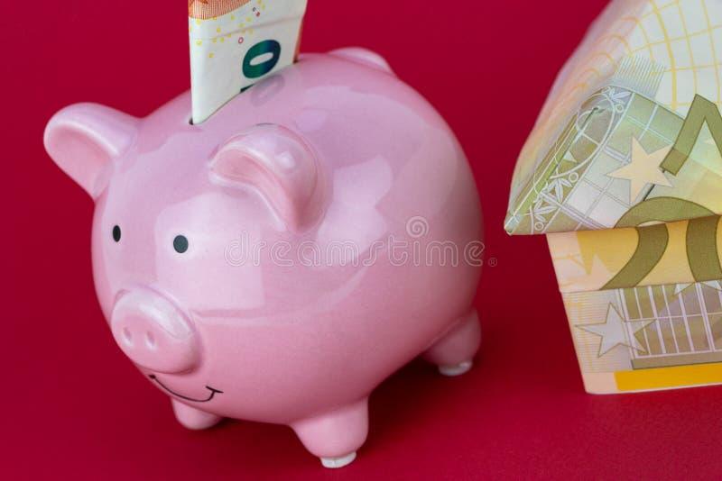 Risparmio ed investimento - porcellino salvadanaio, casa dei soldi sul fondo di colore del lampone immagini stock libere da diritti