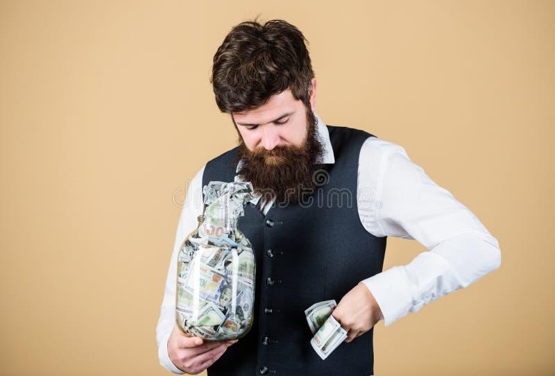Risparmio intascante della società Uomo barbuto che prende il risparmio dei soldi dal barattolo di vetro Uomo d'affari che ruba i fotografie stock libere da diritti