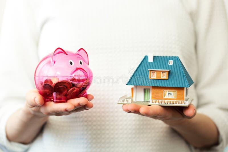 Risparmio per il nuovo concetto della casa della famiglia - porcellino salvadanaio e casa scal fotografia stock