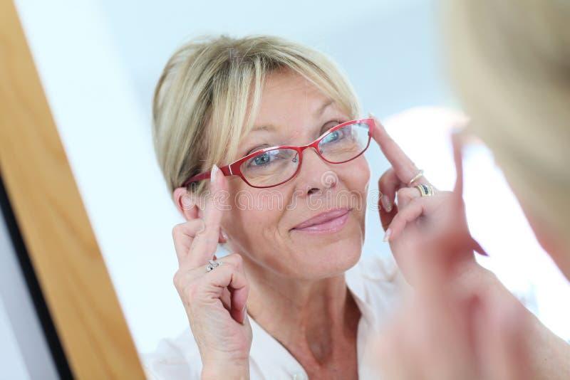 Rispecchi il ritratto della donna senior che prova sugli occhiali fotografia stock libera da diritti