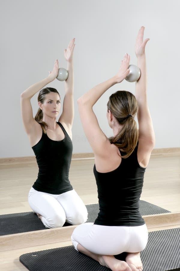 Rispecchi la donna di ginnastica dei pilates che modifica la ginnastica la tonalità di sport delle sfere immagini stock libere da diritti