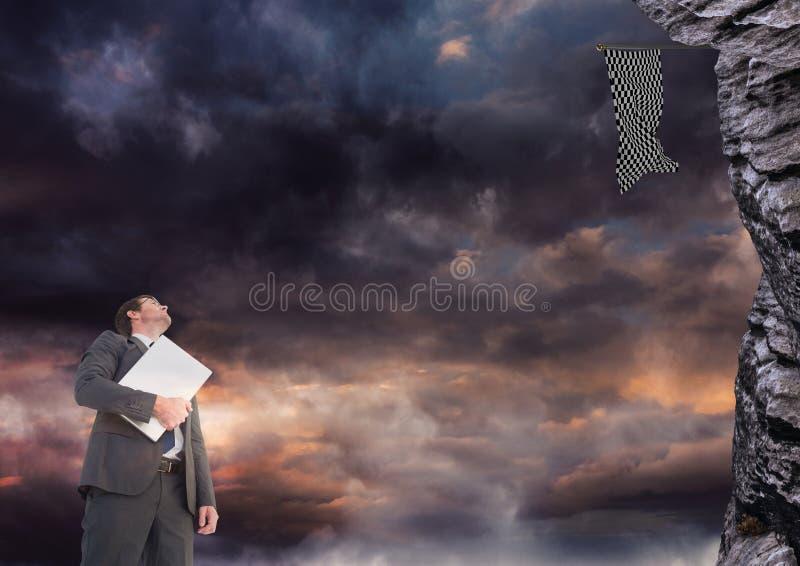 rispettare dell'uomo d'affari vede la bandiera del controllore in una roccia fotografia stock