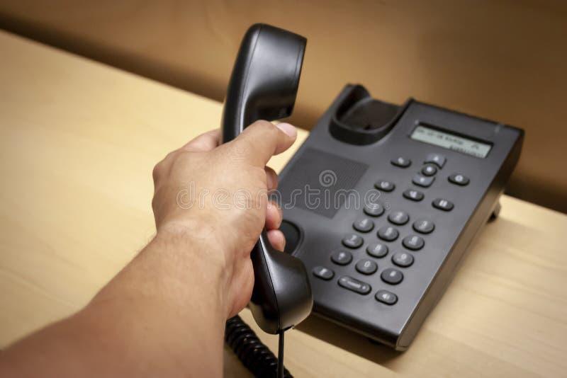 Risposta della chiamata da un telefono nero fotografia stock