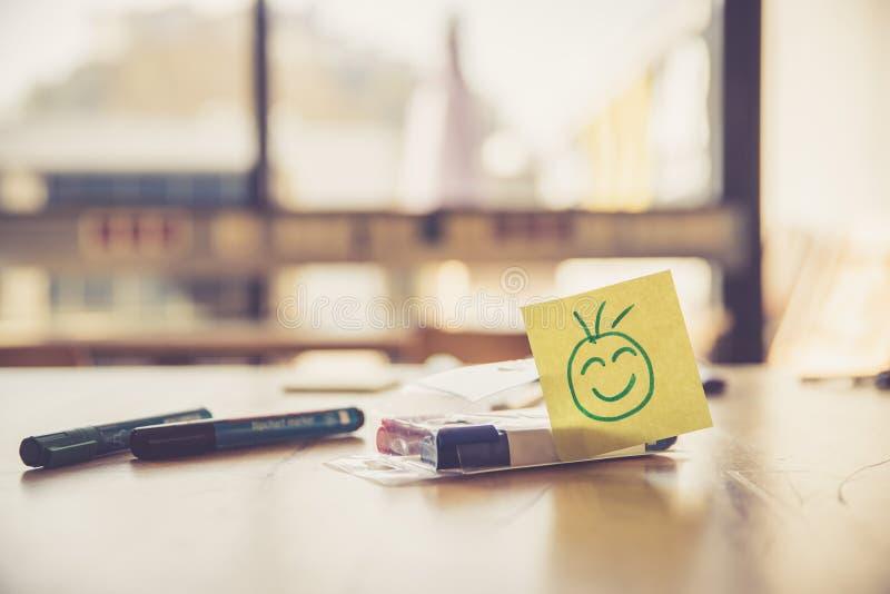 Risposte, motivazione e concetto dell'officina: Smiley Illustration su un posto di lavoro, sulle penne e sulla finestra nei prece fotografia stock libera da diritti