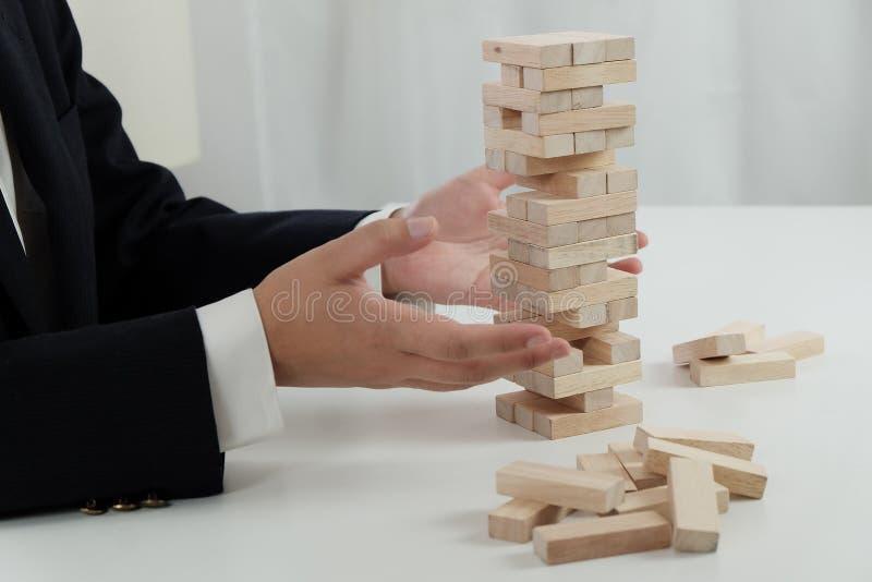 Risque et strat?gie de planification dans l'homme d'affaires jouant pla?ant le bloc en bois photos stock