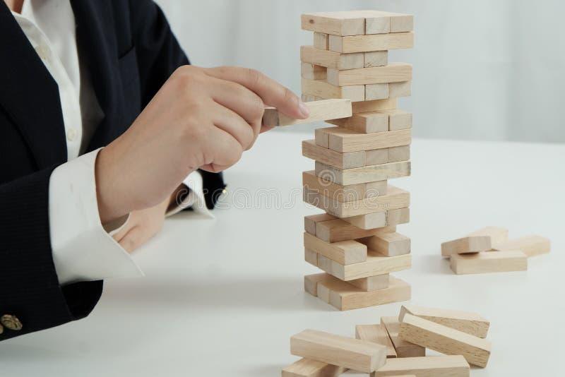 Risque et strat?gie de planification dans l'homme d'affaires jouant pla?ant le bloc en bois Concept d'affaires pour le processus  image stock