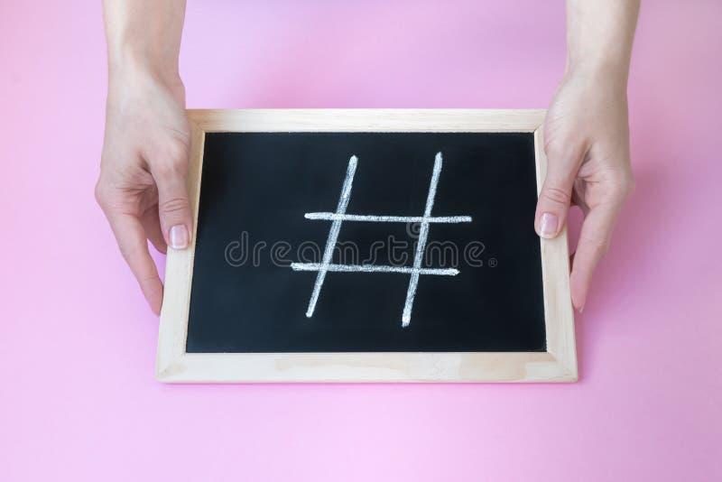 Risque o sinal do hashtag no quadro-negro guardado pelas mãos fêmeas fotos de stock