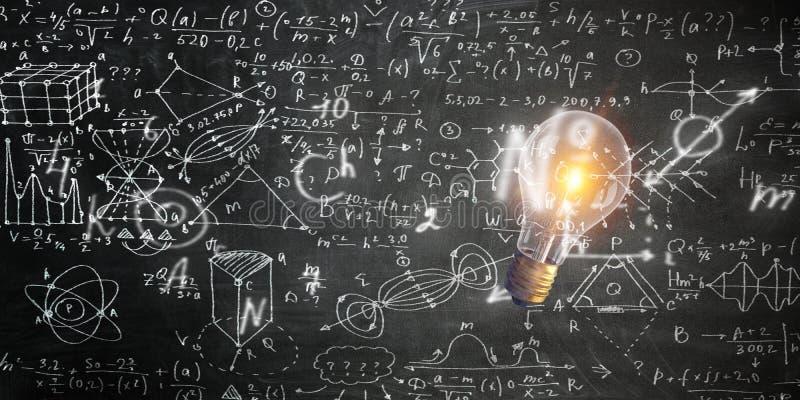 Risque a placa com esboços das matemáticas e fórmulas e uma ampola foto de stock royalty free