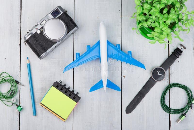 Risquez l'avion de temps, appareil-photo, bloc-notes, les écouteurs, montre sur la table en bois blanche photographie stock libre de droits