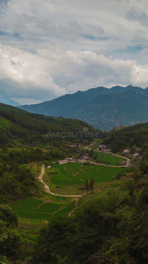 Rissmå pastejer och by med berg i bakgrunden royaltyfria foton