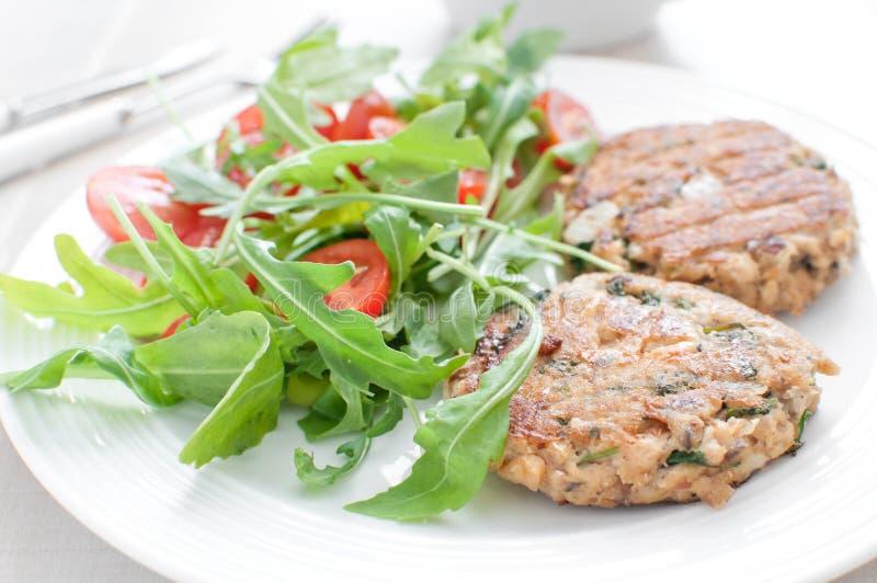 Rissol dos peixes à terra com salada do tomate da rúcula imagens de stock royalty free