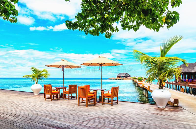 Ristorante con gli ombrelloni su un pilastro di legno contro l'acqua azzurrata dell'oceano fotografia stock libera da diritti
