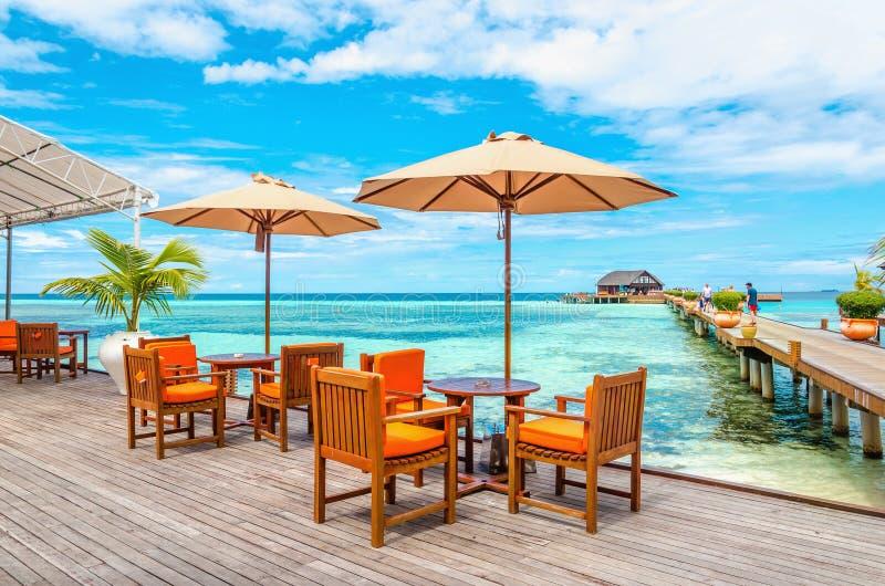 Ristorante esotico sull'acqua, sulle tavole e sulle sedie sotto gli ombrelloni sui precedenti dei bungalow di legno immagine stock
