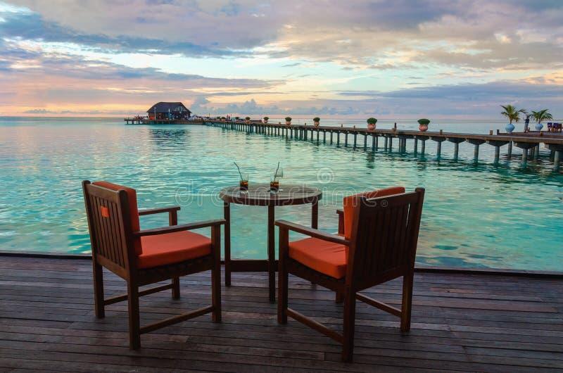 Ristorante sull'acqua sui precedenti di bello tramonto variopinto sopra l'oceano fotografie stock