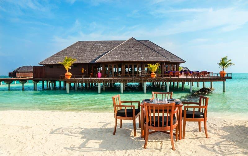 Ristorante variopinto ai precedenti dei bungalow dell'acqua nell'isola tropicale delle Maldive fotografie stock libere da diritti