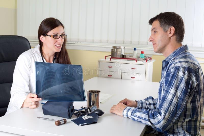 Risultati dei raggi x del dottore Explaining Lung al paziente Medio Evo nella stanza di consulto immagine stock