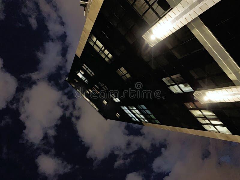Risultato di angolo basso di una costruzione di affari di palazzo multipiano con il cielo nuvoloso nei precedenti immagini stock