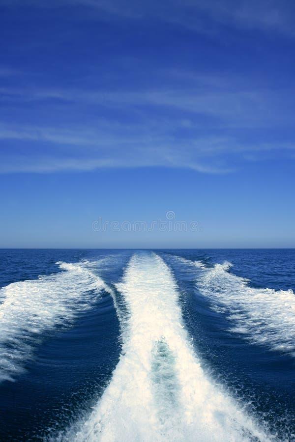 Risveglio bianco della barca sul mare blu dell'oceano immagini stock libere da diritti
