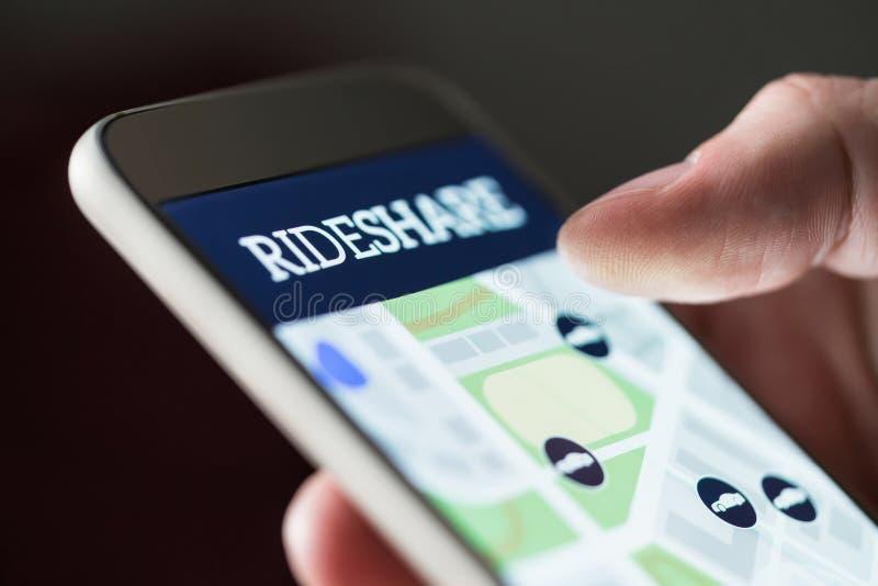 Ritaandeel app in smartphone Mens die rideshare taxitoepassing gebruiken stock afbeelding