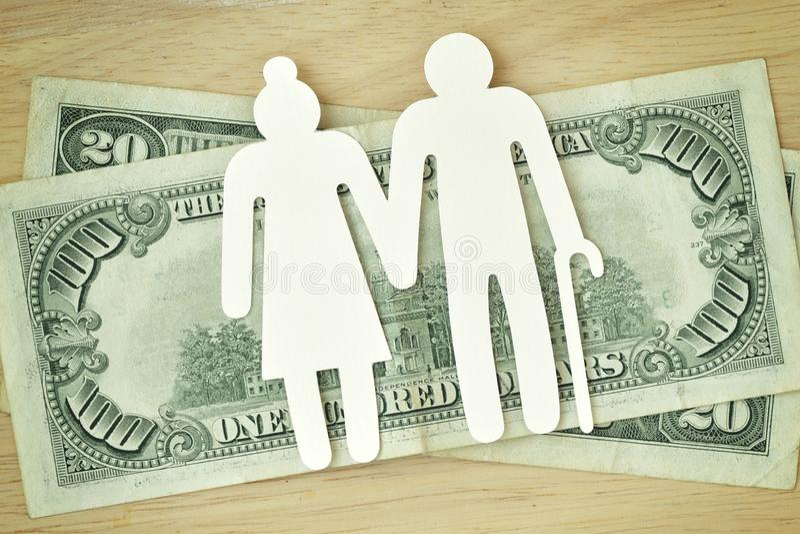 Ritaglio anziano di carta sulle banconote dei dollari - pensione delle coppie concentrata fotografia stock