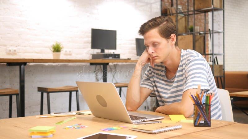 Ritenere malato e stanco Giovane frustrato che dorme sul lavoro immagini stock