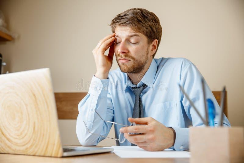 Ritenere malato e stanco Giovane frustrato che massaggia la sua testa mentre sedendosi al suo posto di lavoro in ufficio fotografia stock libera da diritti