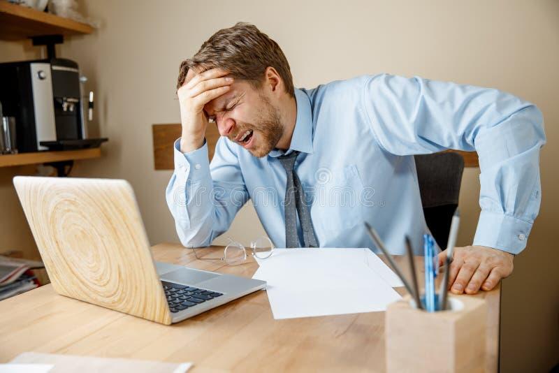 Ritenere malato e stanco Giovane frustrato che massaggia la sua testa mentre sedendosi al suo posto di lavoro in ufficio immagini stock libere da diritti