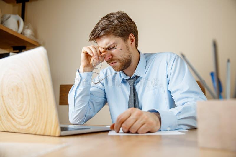 Ritenere malato e stanco Giovane frustrato che massaggia la sua testa mentre sedendosi al suo posto di lavoro in ufficio fotografie stock