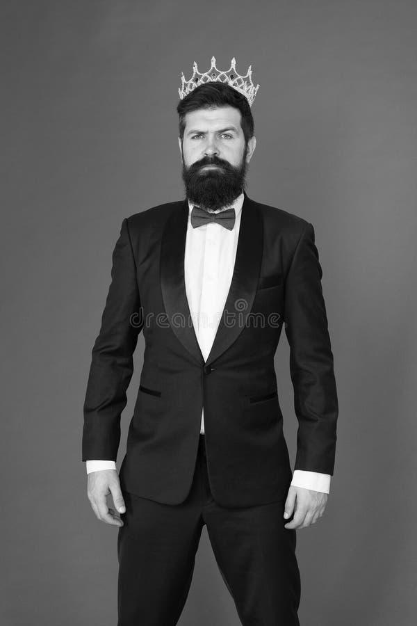 Ritenere superiore Tipo barbuto dell'uomo nel simbolo dorato della corona dello smoking di monarchia Cerimonia di re Attributo di fotografie stock