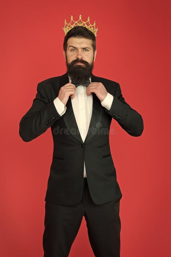 Ritenere superiore Tipo bello barbuto dell'uomo nel simbolo dorato della corona del vestito convenzionale di monarchia Re su ques fotografie stock