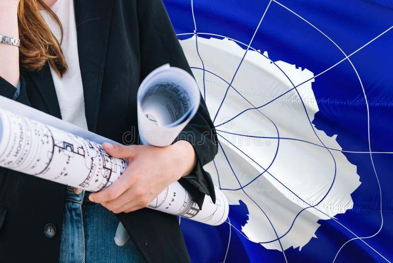 Ritning för arkitektkvinnainnehav mot Antarktis vinkande flaggabakgrund Konstruktions- och arkitekturbegrepp royaltyfri bild
