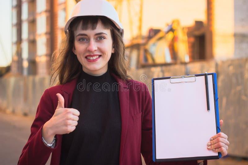 Ritningar för kvinnabyggmästareinnehav, skrivplatta Le arkitektflickan i hjälm på byggnadsbakgrund arkivfoton