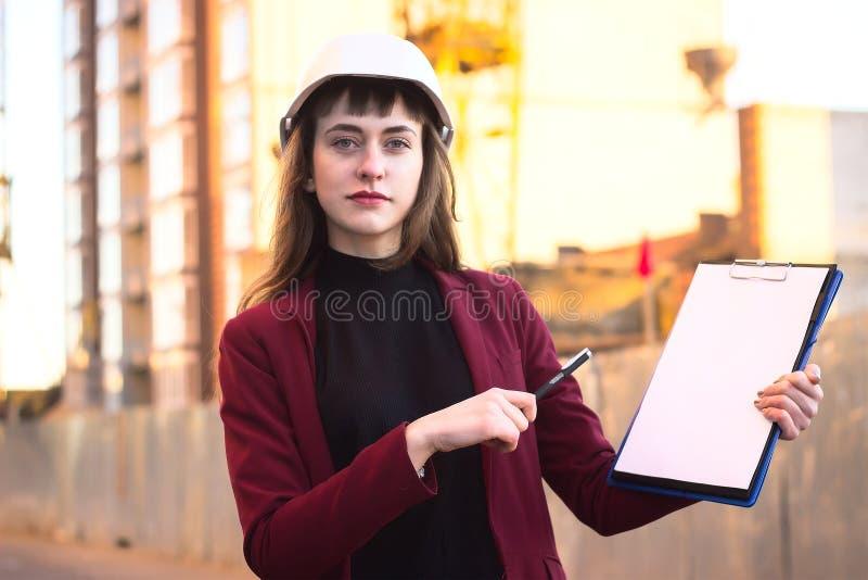 Ritningar för kvinnabyggmästareinnehav, skrivplatta Le arkitektflickan i hjälm på byggnadsbakgrund fotografering för bildbyråer