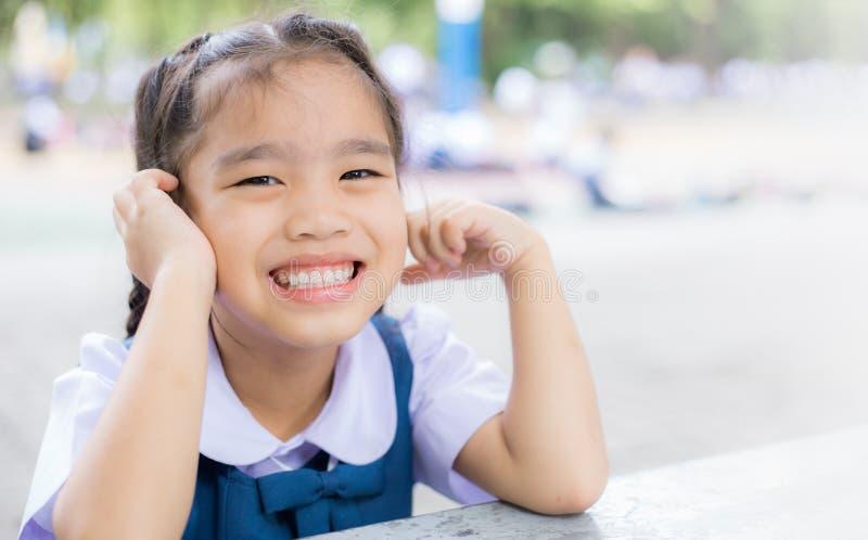 Ritornare felice sorridente all'aperto della ragazza dello studente a scuola fotografia stock