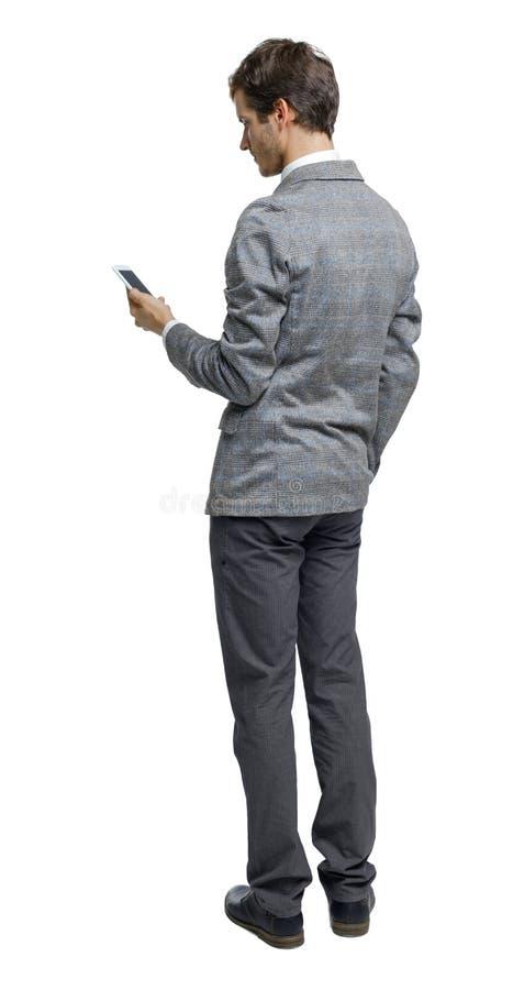 Ritorno di un uomo d'affari che sta analizzando lo smartphone immagine stock