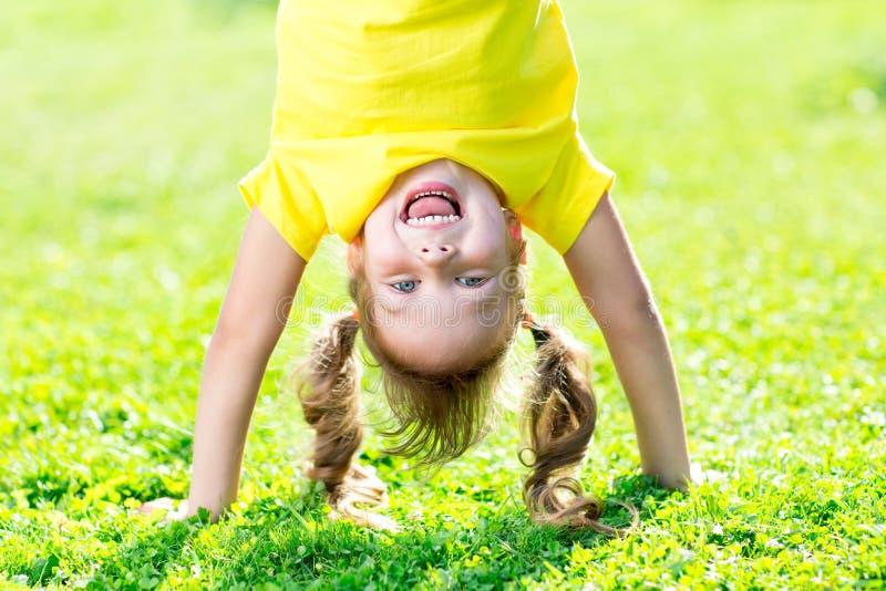 Ritratti del bambino felice che giocano aria aperta capovolta nell'estate che sta sulle mani su erba fotografia stock