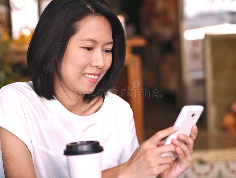 Ritratti della donna asiatica che scrivono al suo schermo dello smartphone con il fronte felice di sorriso in caffetteria accogli fotografia stock