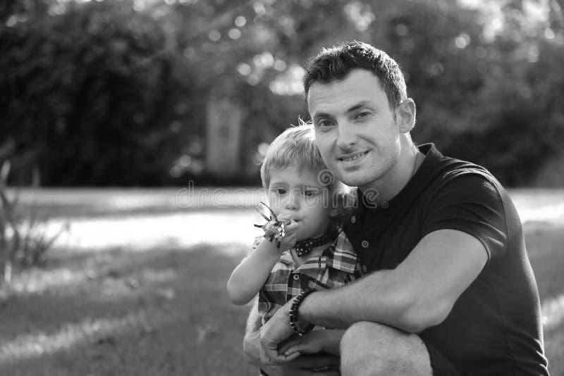 Ritratti di una famiglia europea felice di due genti divertendosi fuori nel bello campo verde della primavera o di estate Il papà immagini stock