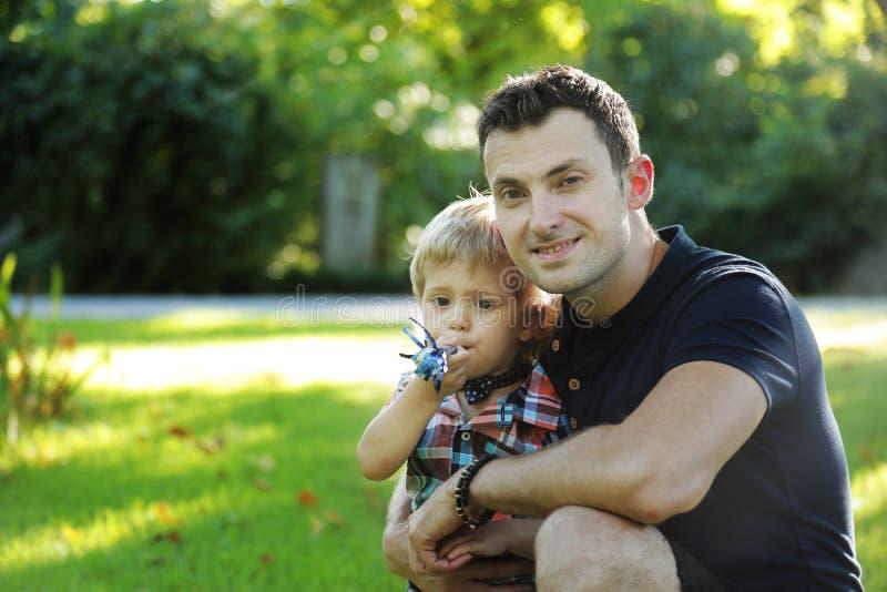 Ritratti di una famiglia europea felice di due genti divertendosi fuori nel bello campo verde della primavera o di estate Il papà immagine stock