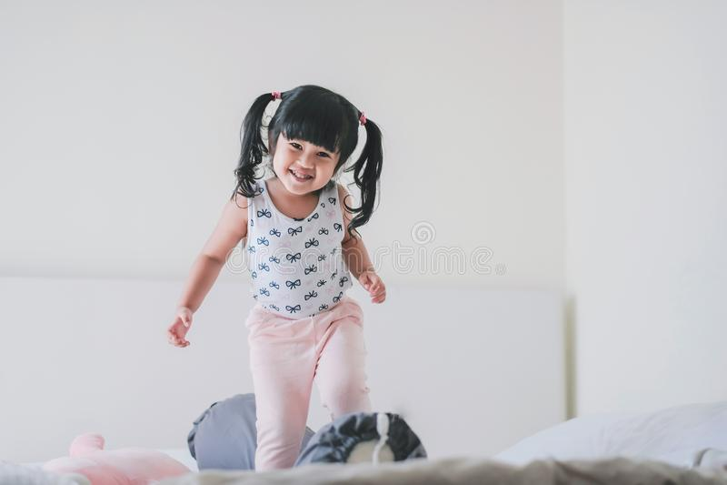 Ritratto adorabile felice dei bambini Una ragazza di tre anni nel momento di felicità in camera da letto immagine stock libera da diritti